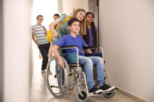 Adolescents dans un couloir d'école, une fille poussant un garçon en fauteuil roulant.