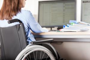 Femme en fauteuil roulant travaillant devant un ordinateur