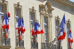 Façade de Mairie avec des drapeaux français aux fenêtres
