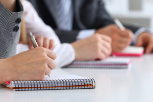 Vue rapprochée de personnes écrivant sur des cahiers pendant une formation ou un cours.