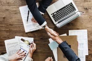 Deux personnes se serrant la main au-dessus d'un bureau