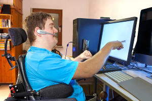Homme en fauteuil roulant pointant un écran du doigt