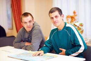 Deux jeunes hommes en situation de handicap assis à un bureau
