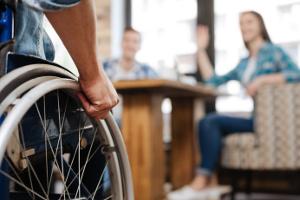 une personne en fauteuil roulant rejoignant deux autres personnes dans un restaurant
