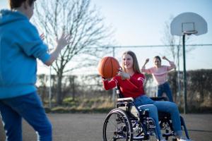 Trois jeunes dont une adolescente en fauteuil roulant jouant au basket